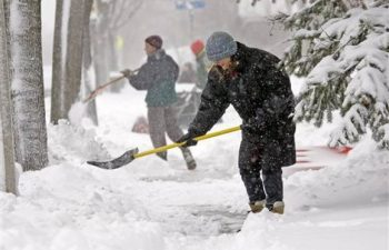 people shoveling snow on a snowy day