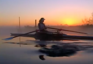 rowing woman with a sunset in the background